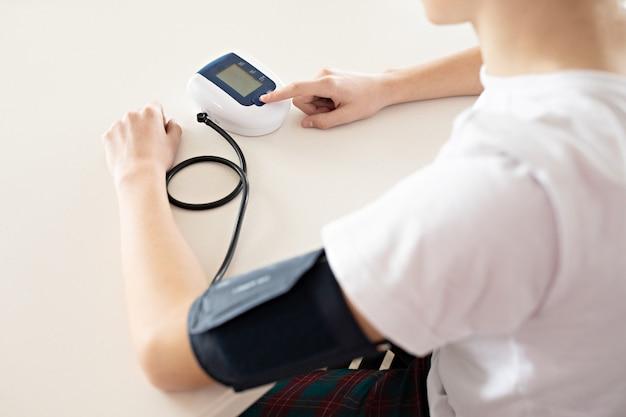 Tiener meet bloeddruk met monitor in huis.