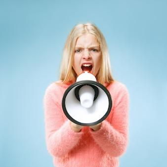 Tiener meisje aankondiging met megafoon op blauwe studio