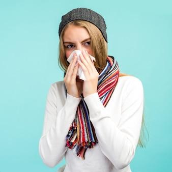 Tiener meisje blaast neus in weefsel