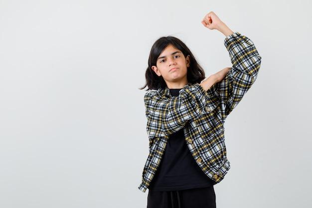 Tiener meisje hand op armspieren in casual shirt en peinzend op zoek. vooraanzicht.