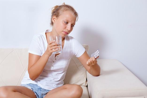 Tiener meisje houdt pil en glas water pijnstiller medicijnen drugs te nemen om hoofdpijn pijn te verlichten.
