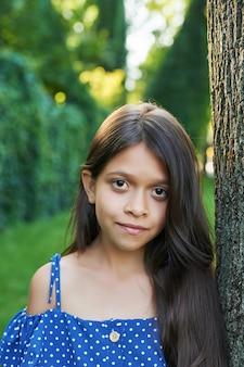 Tiener meisje in de buurt van een boom in een zomer park bij zonsondergang