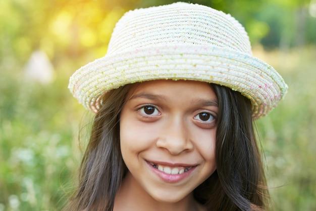 Tiener meisje in een hoed in een veld bij zonsondergang