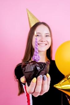 Tiener meisje in gouden verjaardag cake met kaars, een wens maken over roze achtergrond focus op voorgrond