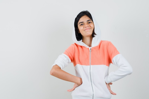 Tiener meisje in sweatshirt handen op haar middel zetten en zelfvoldaan kijken.