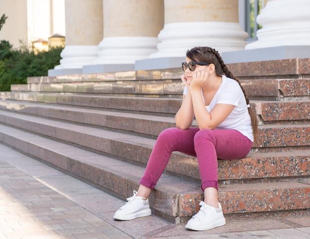 Tiener meisje in zonnebril zit op de trap wegkijken