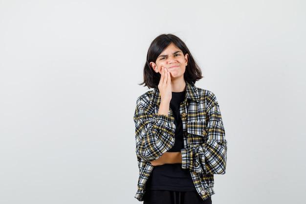 Tiener meisje kiespijn in casual shirt lijden en op zoek pijnlijk. vooraanzicht.