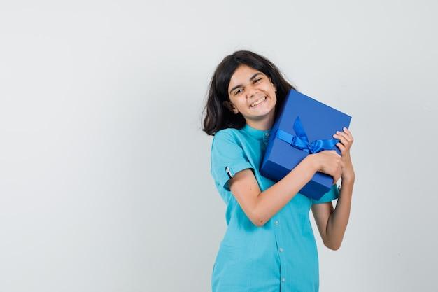 Tiener meisje knuffelen haar huidige doos in blauw shirt en kijken vrolijk