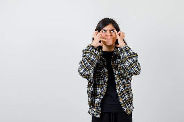 Tiener meisje met handen in de buurt van gezicht, wegkijken in casual shirt en besluiteloos op zoek. vooraanzicht.