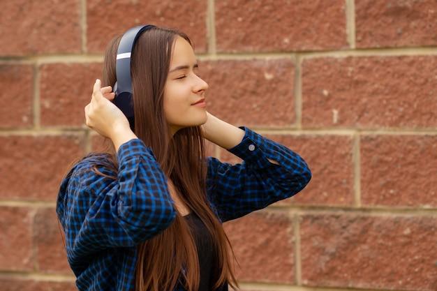 Tiener meisje met koptelefoon luisteren naar muziek aan de telefoon, wandelen, dansen in de zomer, levensstijl