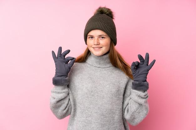 Tiener meisje met winter hoed met een ok bord met vingers