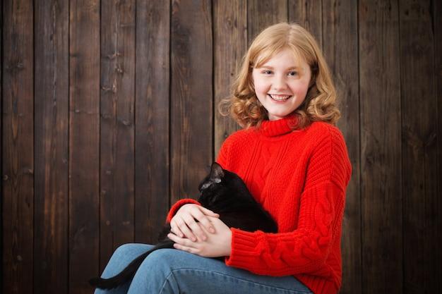 Tiener meisje met zwarte kat op oude houten