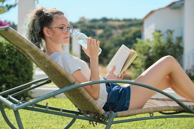 Tiener meisje ontspannen buiten zittend in rotan stoel op groen gazon