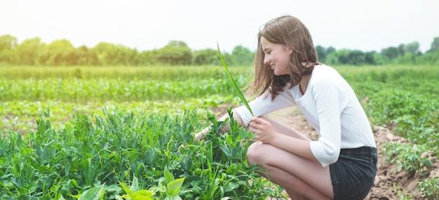 Tiener meisje raakt handen met groene planten in de tuin