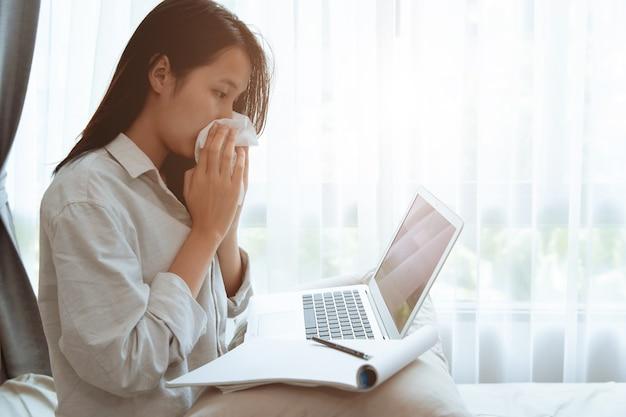 Tiener meisje veegt neus af tijdens online homeschooling met griepziekte coronavirus (covid-19) besmet, thuis blijven werken met laptop, zelfzorg tijdens het afsluiten van de stad.