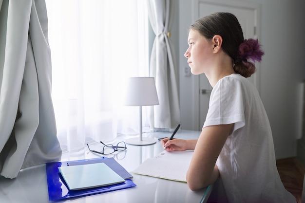 Tiener meisje zit studeren aan bureau thuis in de buurt van venster, student schrijven in notitieblok