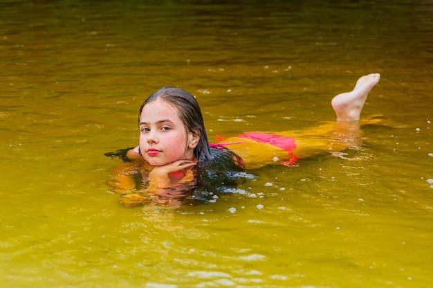 Tiener meisje zwemt in een kleine rivier. tienermeisje geniet van het warme weer tijdens de zomervakantie