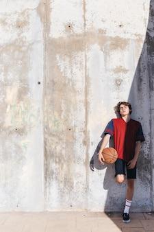 Tiener met basketbal die op muur leunt