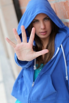 Tiener met blauwe sweater die hand toont aan camera
