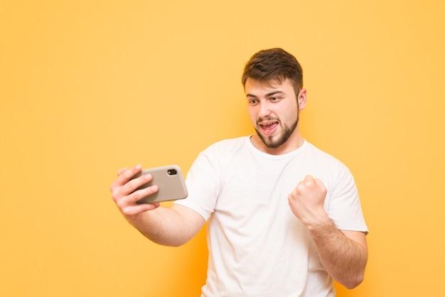 Tiener met een baard die mobiele games op smartphone speelt, naar het scherm kijkt en zich verheugt