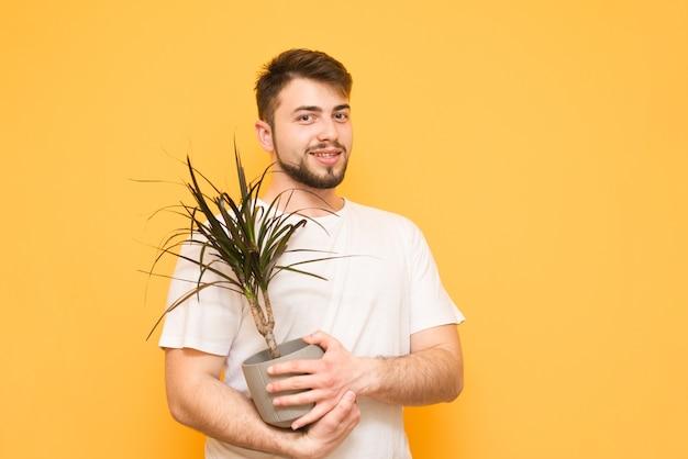 Tiener met een baard staat op geel en houdt een bloempot met een plant in zijn handen