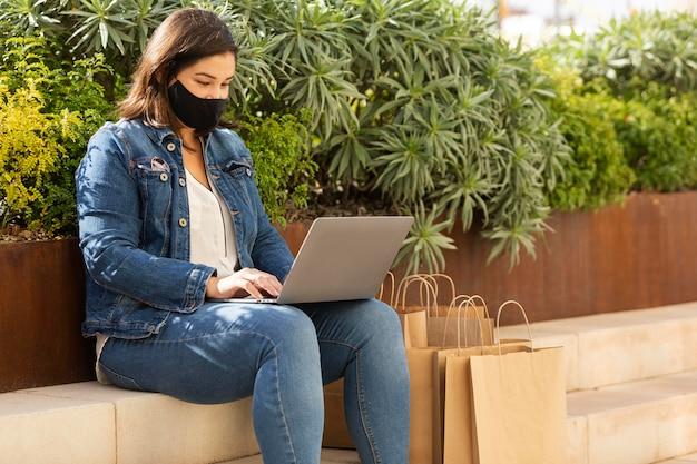 Tiener met een gezichtsmasker dat haar laptop doorbladert