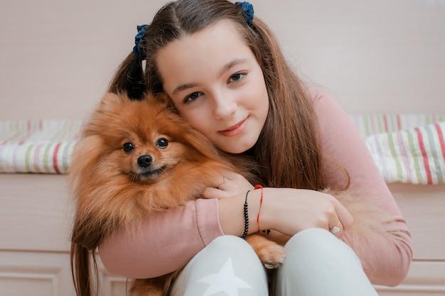 Tiener met een hondenras spitz verheugt zich thuis met een huisdier op de vloer.