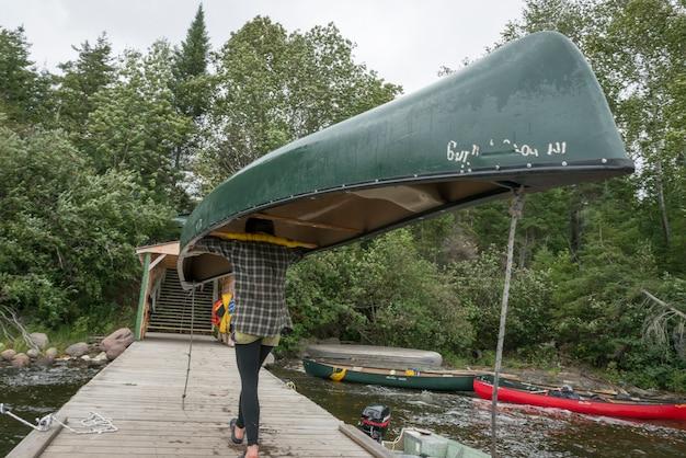 Tiener met een kano op haar hoofd, bb camp, lake of the woods, ontario, canada