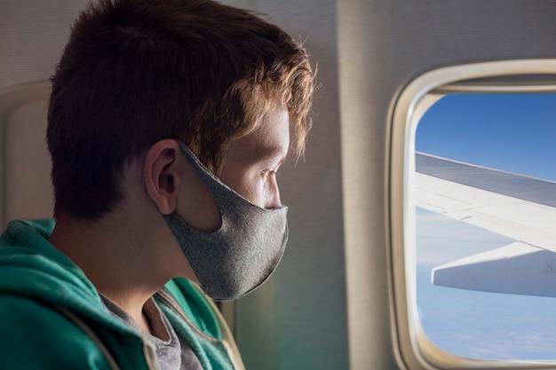 Tiener met een medisch masker kijkt in het vliegtuigraam jongen in het vliegtuig