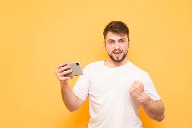 Tiener met een smartphone in zijn hand, gekleed in een wit t-shirt