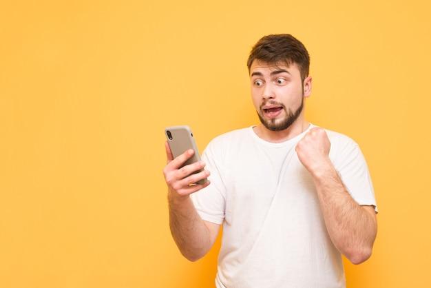 Tiener met een wit t-shirt, staande op geel en verward kijkend naar een smartphone in zijn hand.