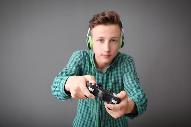 Tiener met gamepad op grijs