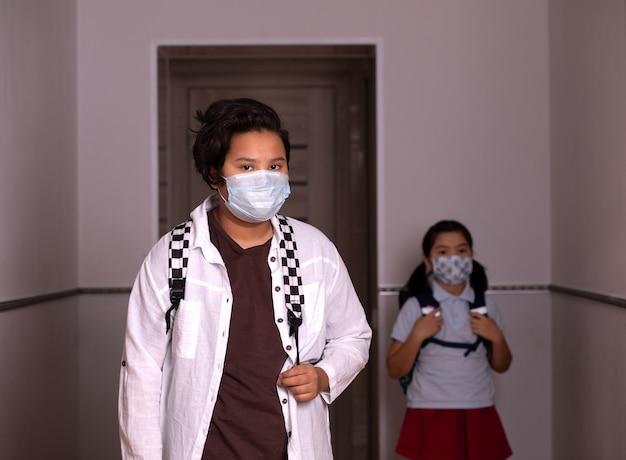 Tiener met gezichtsmasker gaat terug naar school na covid-19 quarantaine en lockdown. op de achtergrond een kind van de basisschool. kinderen met maskers voor coronaviruspreventie.