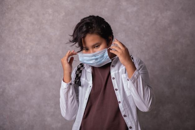 Tiener met gezichtsmasker gaat terug naar school na covid-19 quarantaine en lockdown. tiener met maskers voor coronaviruspreventie.