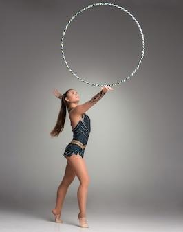 Tiener met haar haar die gymnastiekdans doet met gekleurd lint op een grijze achtergrond