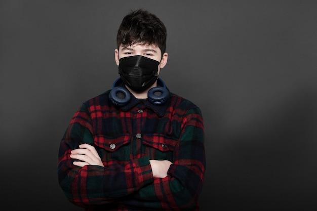 Tiener met hoofdtelefoons en medica-masker in studio met grijze achtergrond