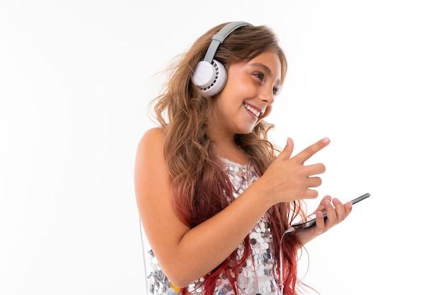 Tiener met lang blond haar geverfd met tips roze, in glanzende lichte jurk, permanent met koptelefoon en telefoon in de hand te houden