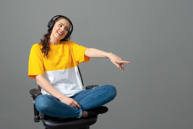 Tiener met lang golvend haar gekleed in een geel t-shirt zittend op een bureaustoel en luisteren naar muziek