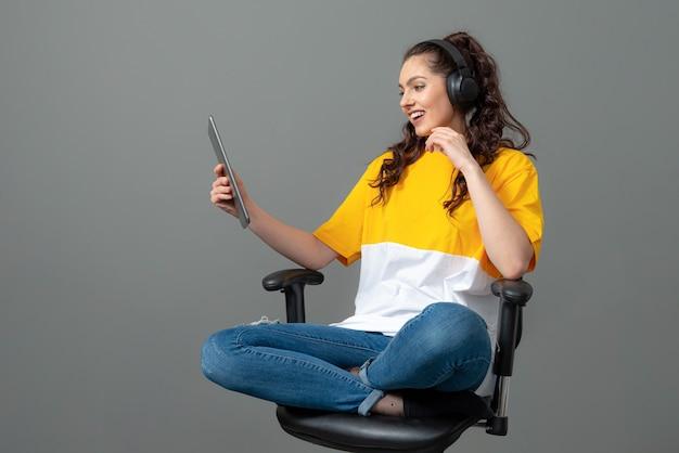 Tiener met lang golvend haar gekleed in een geel t-shirt zittend op een bureaustoel en met behulp van tablet, videobellen, geïsoleerd op een grijze muur