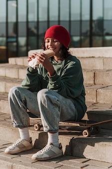 Tiener met lunch in het park op skateboard