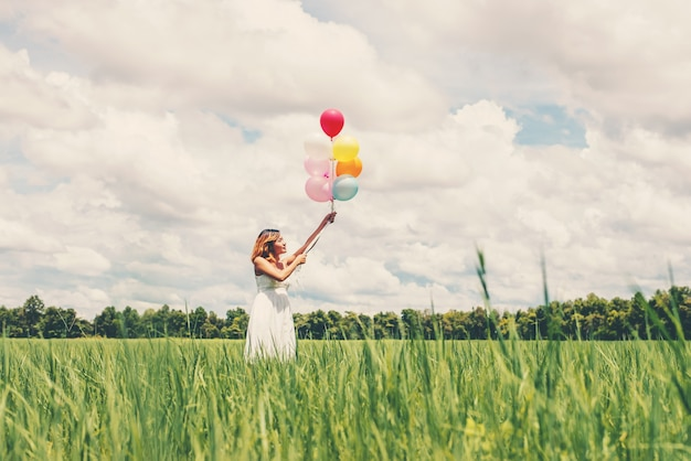 Tiener met plezier met ballonnen in openlucht