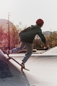 Tiener met plezier met skateboard in het park
