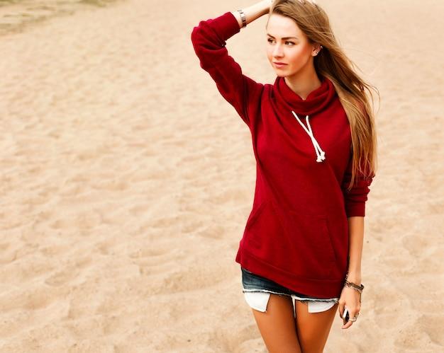Tiener met rode sweater en shorts
