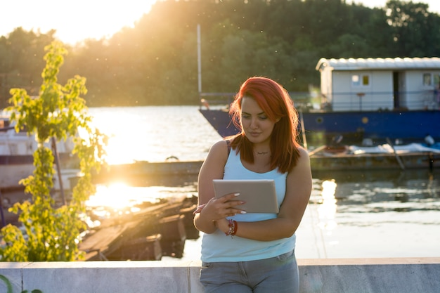 Tiener met rood haar die dichtbij de rivier ontspannen