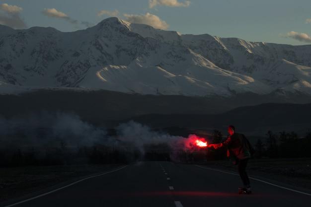 Tiener met rood vuur van het namaak met een skateboard rijden op weg in bergen