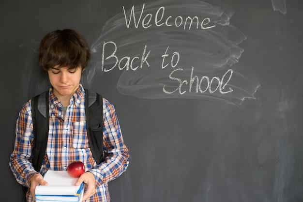 Tiener met rugzak, boeken en appel met terug naar school op zwarte raad