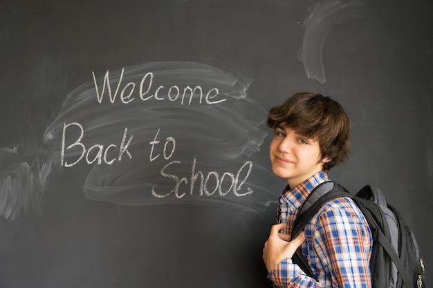 Tiener met rugzak en terug naar school die op zwarte raad wordt geschreven