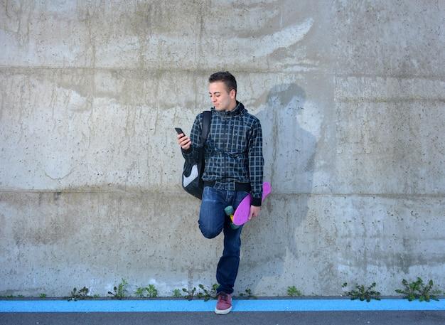 Tiener met skate die op uw smarphone let