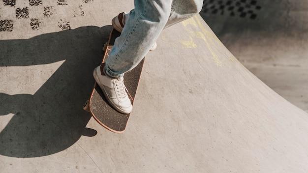 Tiener met skateboard met plezier in het skatepark en kopieer de ruimte