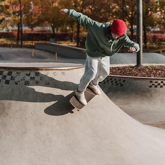 Tiener met skateboard met plezier in het skatepark